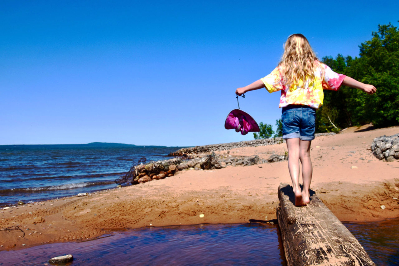 A young child with outstretched arms, in a yellow shirt, balances while she crosses a log over water at a beach.