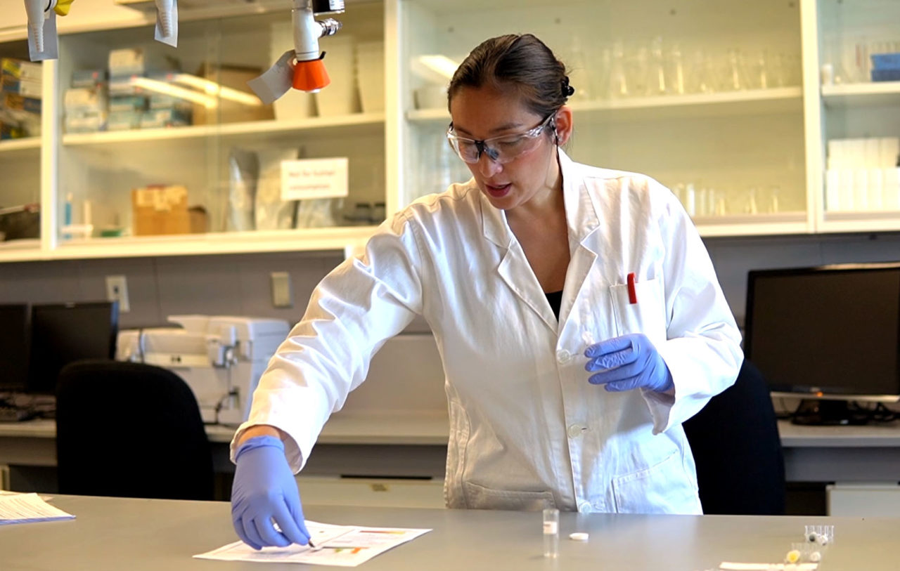 Dr. Elaine Ho-Tassone works in a lab, comparing a lab sample to a piece of paper.